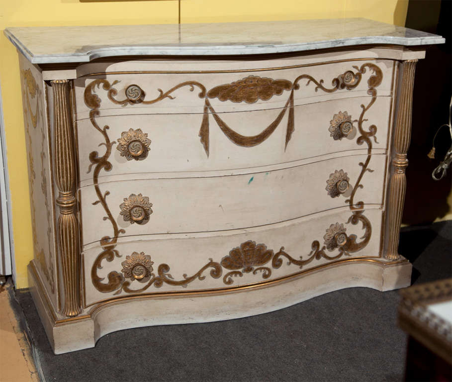 Pair of attractive French commodes, circa 1950s, the white serpentine marble atop a white distress-painted and parcel-gilt conforming case, fitted with four graduating drawers decorated with painted scrolls, flanked by fluted balusters, raised on
