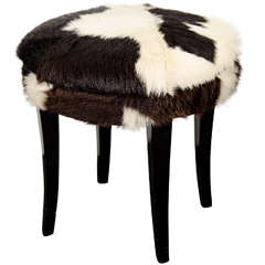 A Mid Century Stool with Cow Hide Upholstery and Ebonized Legs