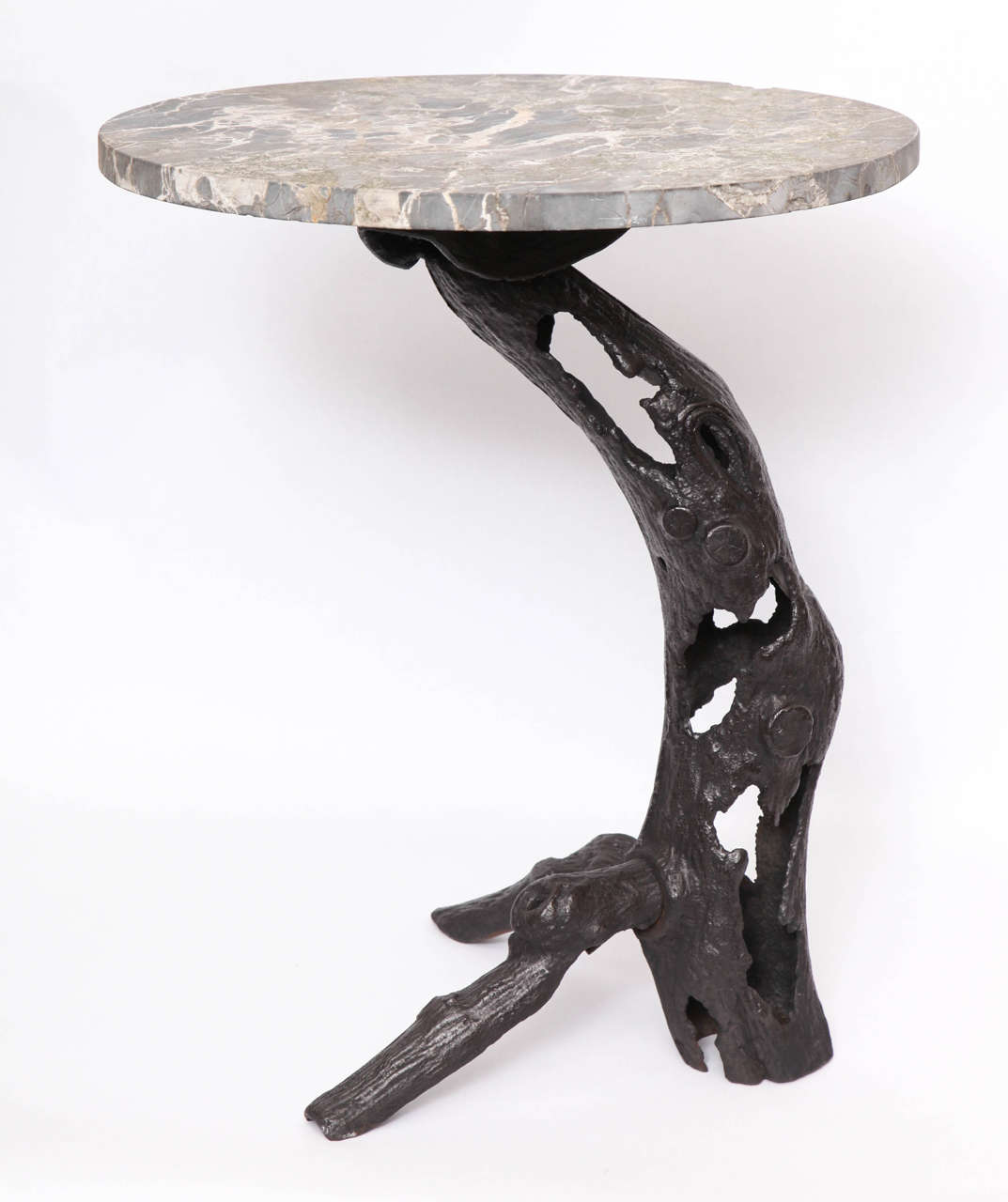 A 1920s sculptural patinated iron and marble table.