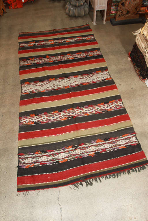 Vintage Moroccan flat-woven Tribal Kilim rug from the Middle Atlas of Morocco, North Africa.  Handwoven in stripes of red and dark green, black and white geometrical Tribal designs. Each carpet is a unique work of Art, handwoven by Berber Women