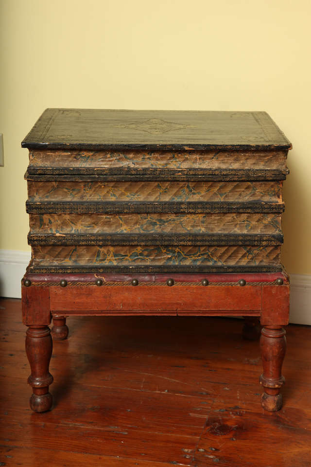 """Victorian gilt tooled blue faux leather side table in the form of a stack of four books raised on a red leather cushion with applied trim and brass nailheads, on four turned red stained legs. The hinged """"books"""" gilt stamped on their bindings"""
