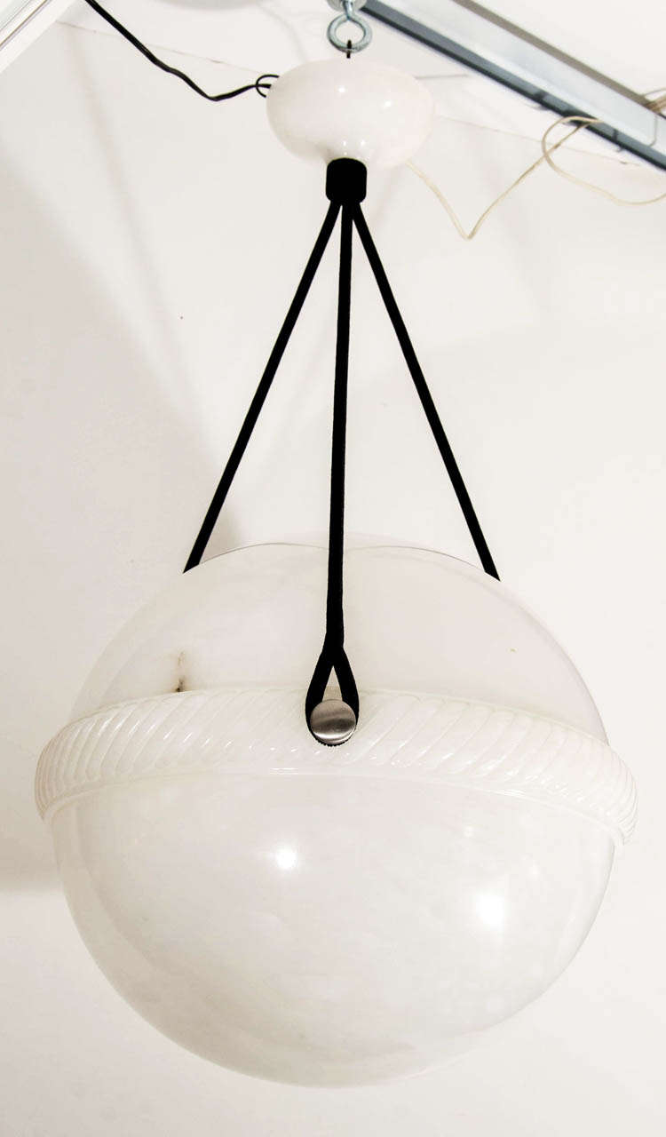 Carved from two pieces of lightly veined alabaster, the upper bowl rests on a carved, twirled rope rim. Three holes strategically placed out of sight, allow ventilation  as well as easy access to change bulbs.   Suspended on a set of three