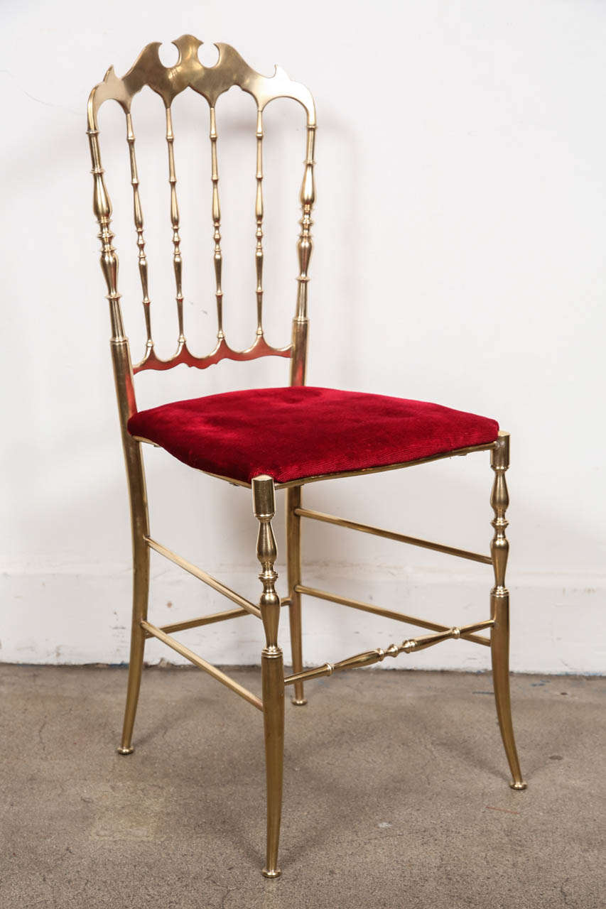 Set of two stunning Italian polished brass Chiavari chairs with bat motif and red velvet original upholstery, circa 1950s.