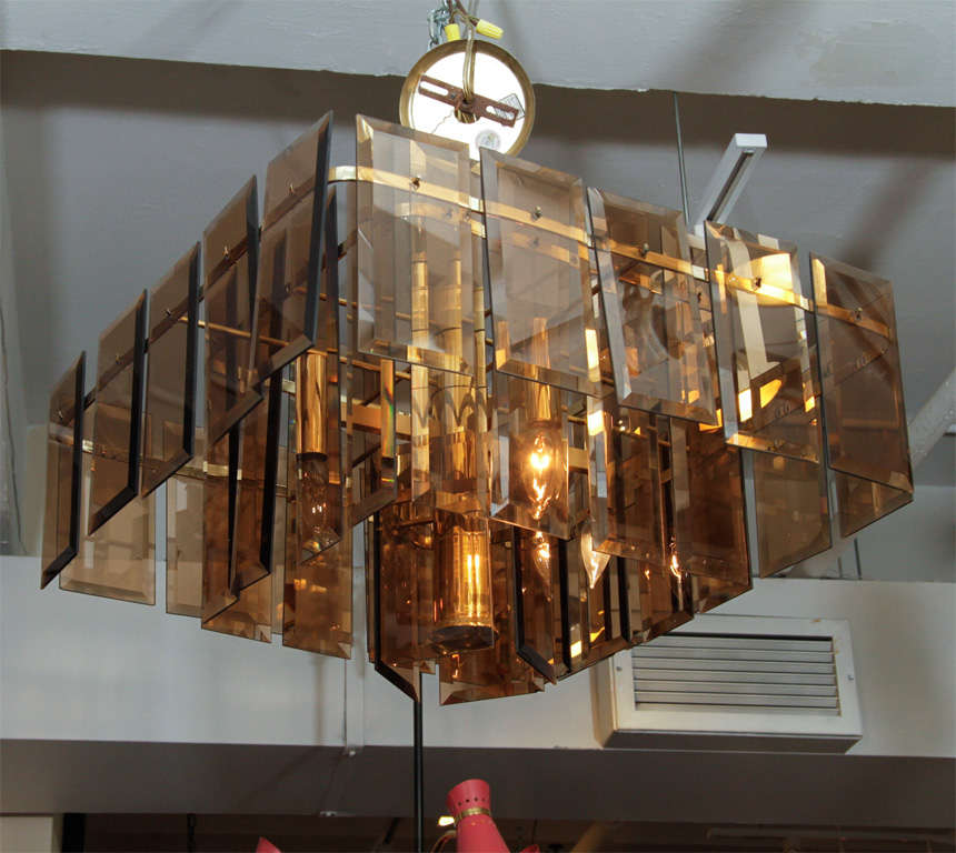 Three tiers of faceted smokey amber glass mounted on a polished brass plate frame, with five downward lights.