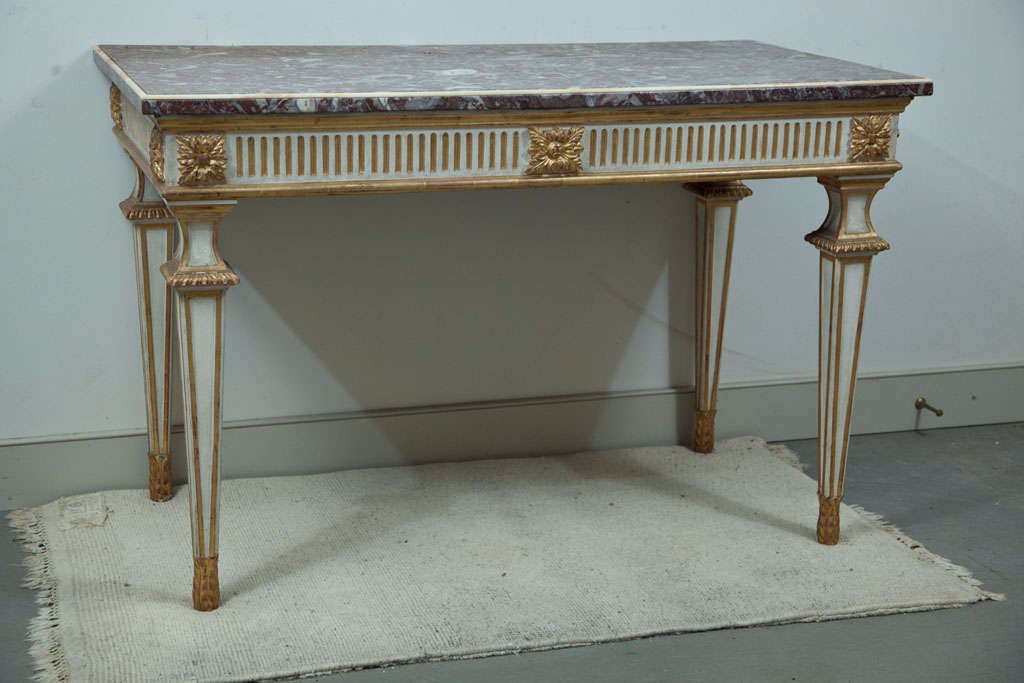 This handsome neoclassical table in cream paint and parcel-gilt has a fluted apron with foliate carvings while the rose marble top has a cream marble beaded edge. Perfectly sized for a large center hall or salon, it would be quality addition of