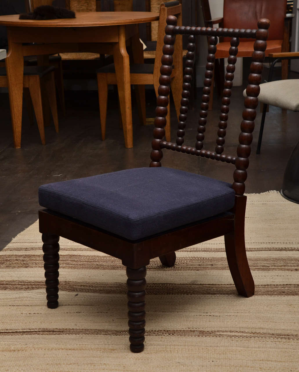 Bobbin style side chair with three-spindle backrest. Newly upholstered navy linen seat cushion.