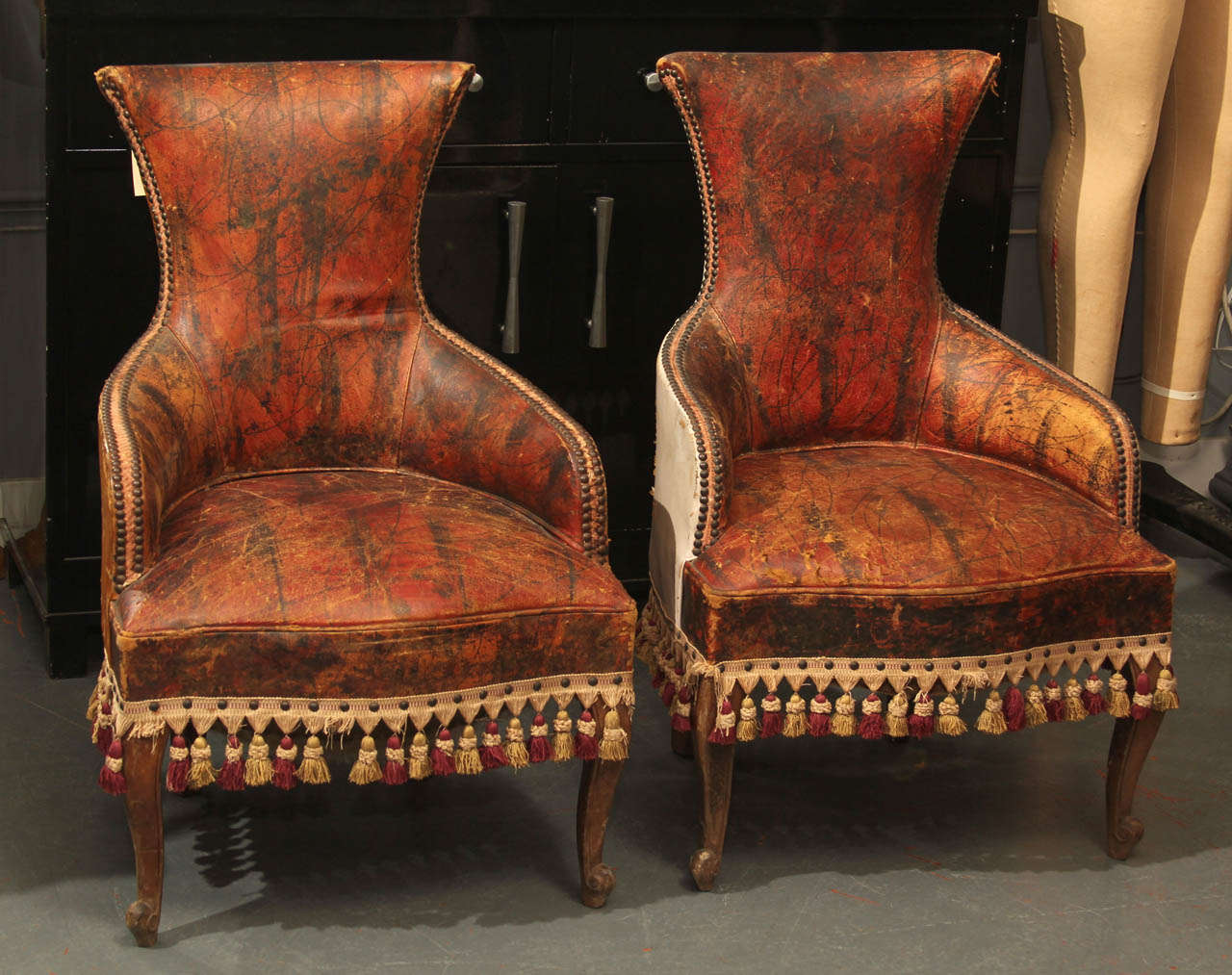 Unusual pair of curvy faux finished leather child size chairs trimmed in tassels and nailheads, as found.