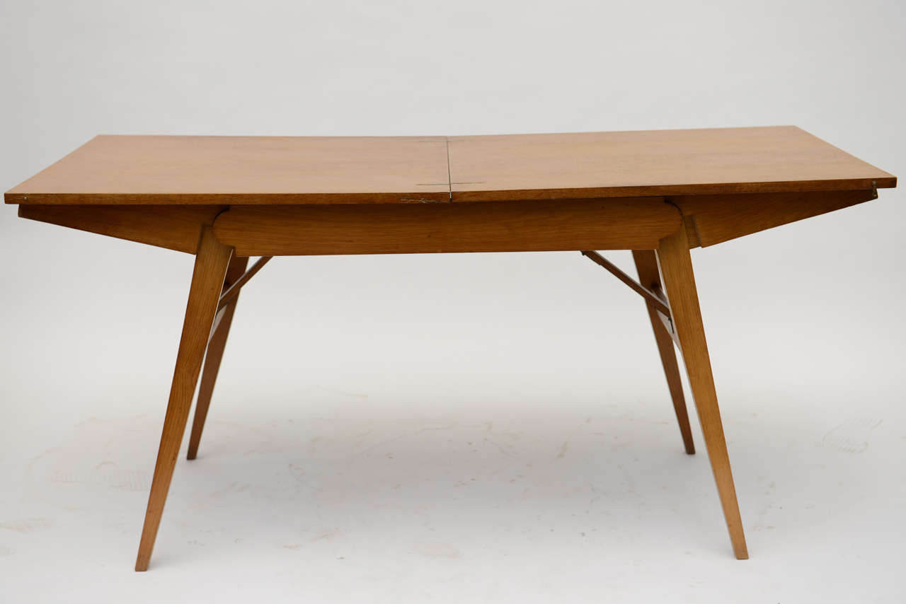 This is two pieces in one.  Shown as a desk, dining room table, but with one easy movement (no removable parts of assembly) you can drop this down to a stylish cocktail table.