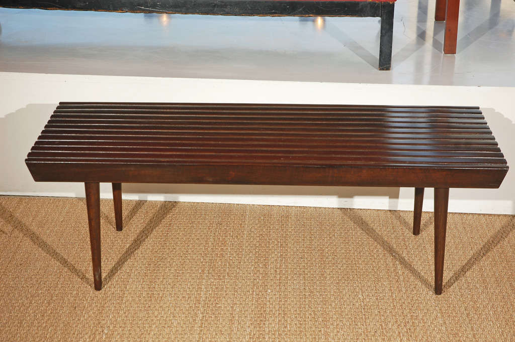 Classic and inimitable, this Nelson slat bench in an ebony finish is the perfect piece for an entryway or transitional space and outstanding at the foot of a bed.