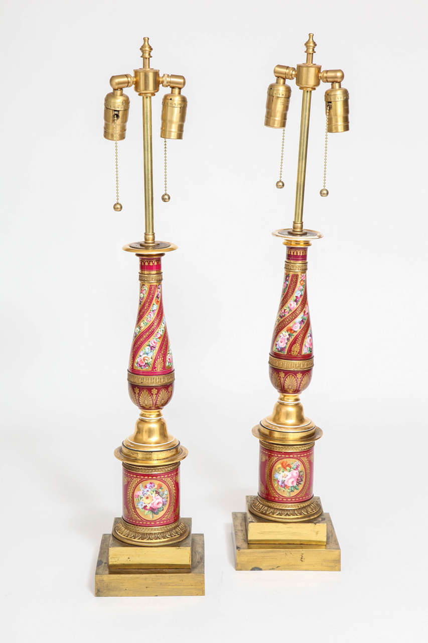 Pair of antique French Empire red porcelain and ormolu-mounted lamps, attributed to Sèvres. The porcelain bases of the lamps are decorated with ovals depicting bouquets of hand painted multicolored flowers on a red porcelain background. The main