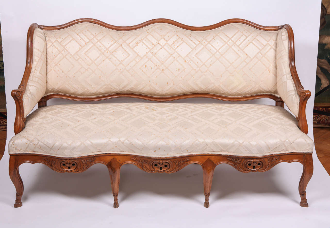 A FINE FRENCH 18th CENTURY CARVED WALNUT CANAPE WITH A SHAPED BACK , SCROLLING ARMRESTS ON A SERPENTINE SEAT ON CABRIOLE LEGS ENDING IN SCROLL FEET. CM 165X90X65