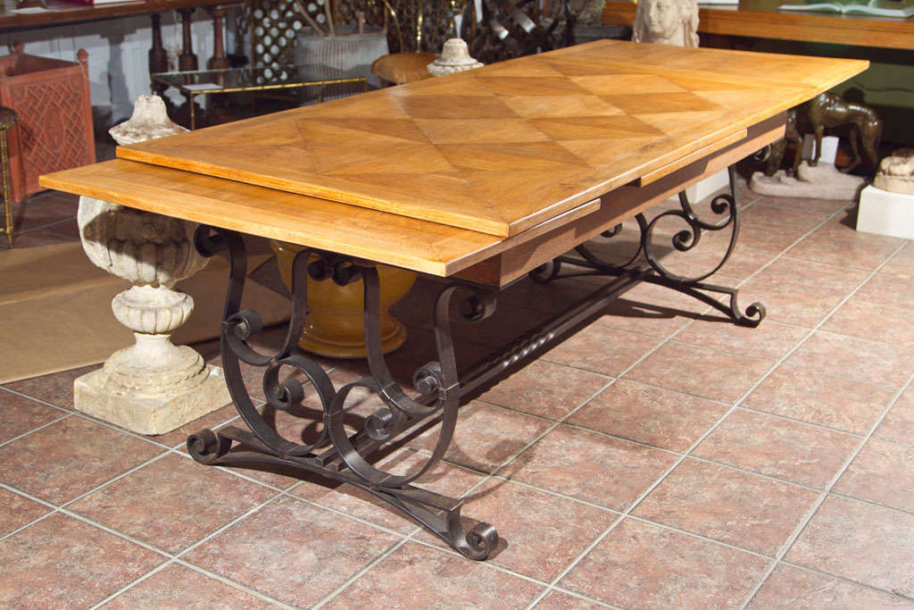 Oak parquet top with pull out leaves on a black scroll design wrought iron base