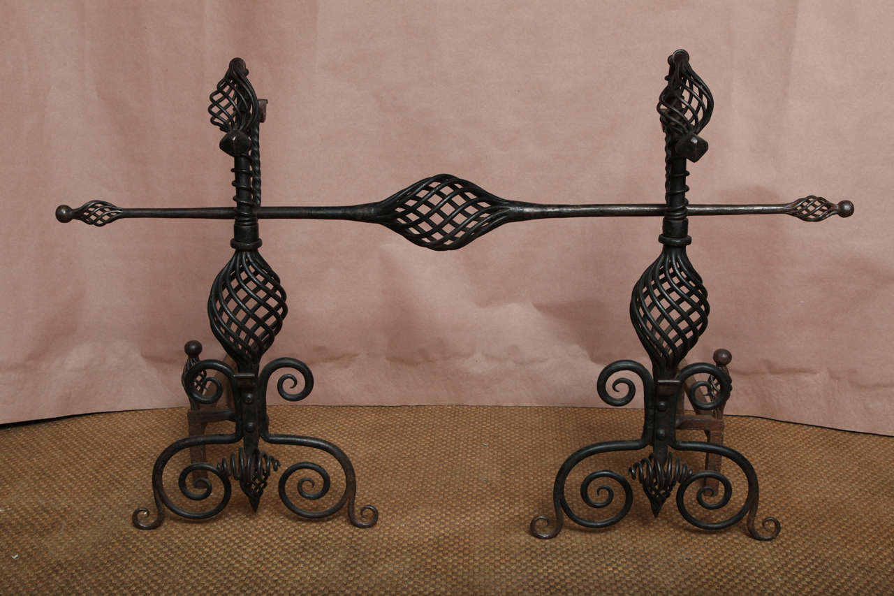 A pair of Arts and Crafts andirons with open wrought iron twist work bodies and scrolled supports with finials, and  pivoting spit supports, retaining original matching spit.   Impressive design and scale.