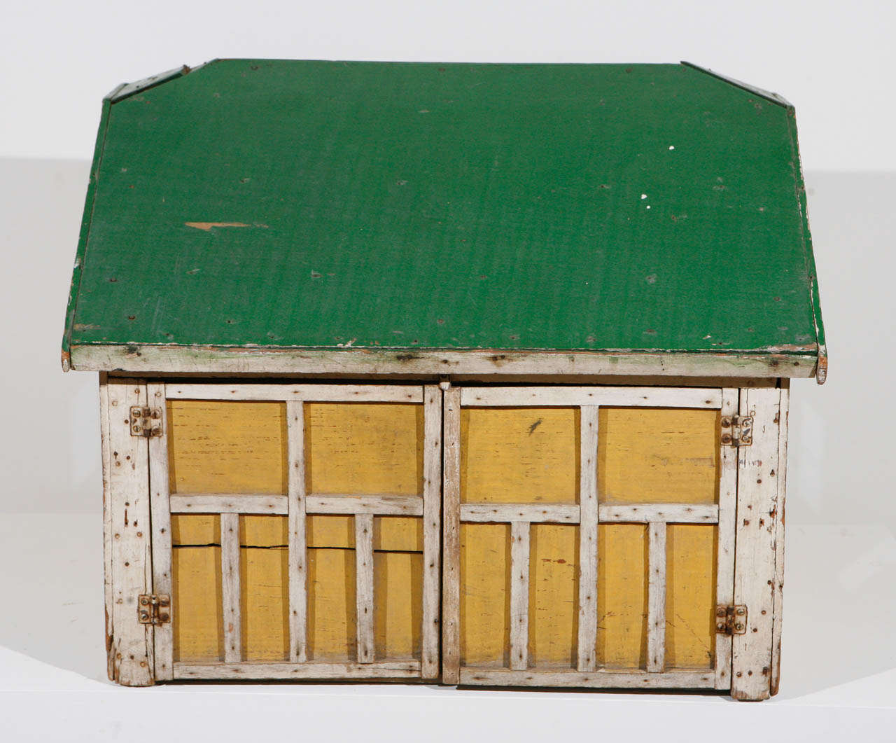 A wooden architectural model in original paint of a garage or barn structure, likely used as a child's play object, with a single door and three windows, along with a highly detailed set of double doors, which open on hinges. Made of scrap wood,
