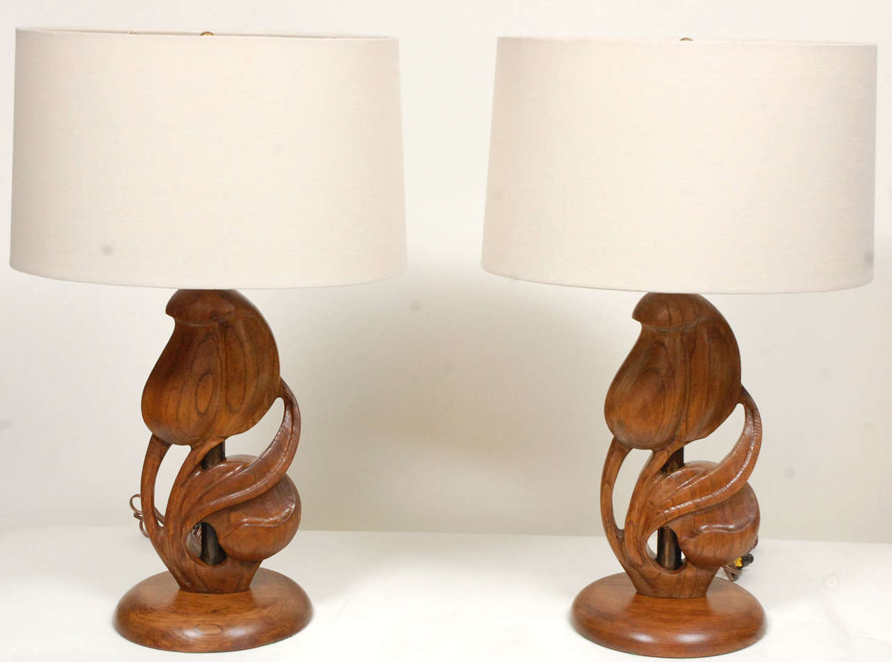 A good pair of free flowing Heifetz table lamps in carved wood with new linen shades. The decorative elements are floral on a nature,  have pierced carving features and stand on round bases.