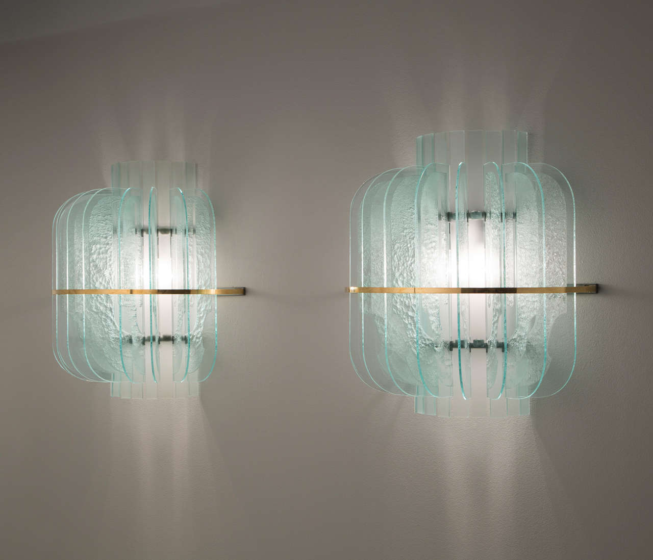 Set of five wall lights, in glass, metal and brass, Italy, 1950s.   Set of five large wall lights in structured glass and brass details. These lights are designed in the manner of Fontana Arte. A halve round design featuring nine structured and