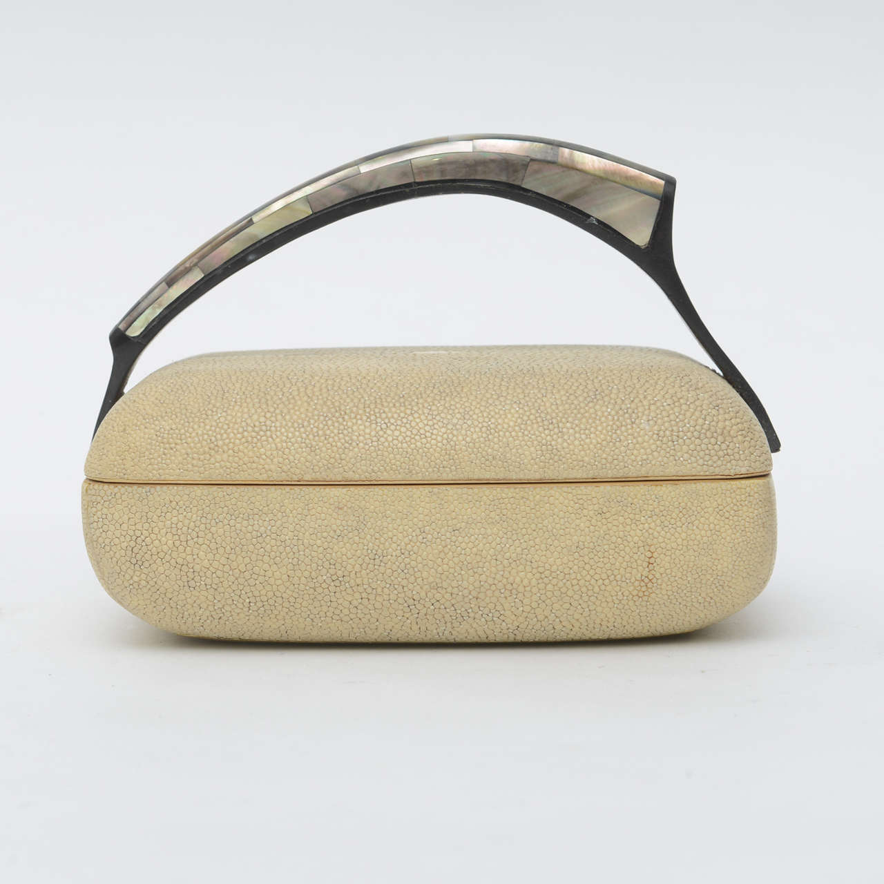 The mother-of-pearl covered handle over a lidded box in shagreen, marked R and Y Augousti on bottom.