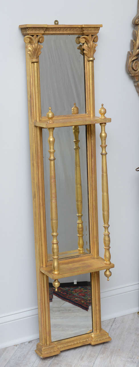 Elegant pair of gilded mirrored wall hangings with two shelves and beautifully carved column details.