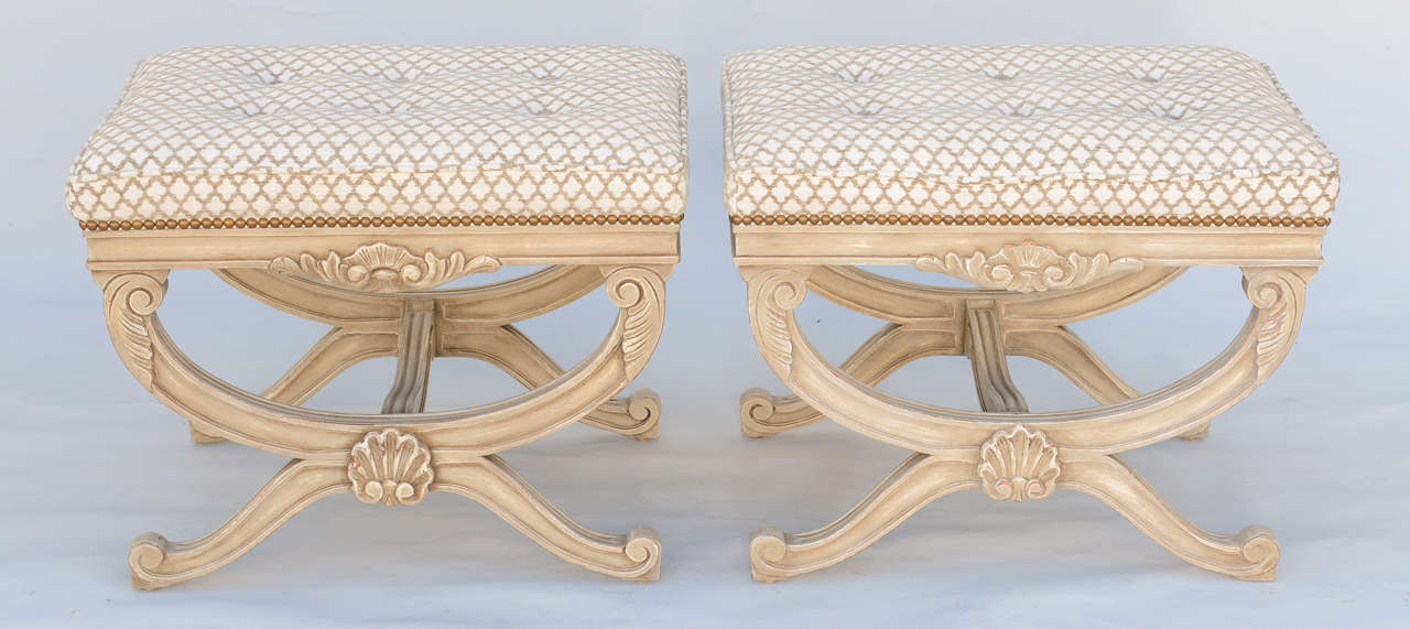 Pair of curule-form stools,or ottomans, each having rectangular boxed seats, upholstered with nailheads, on bases with painted finish; each fielded apron decorated by outcarved seashell, raised on foliate-headed reeded X-frame legs, joined by