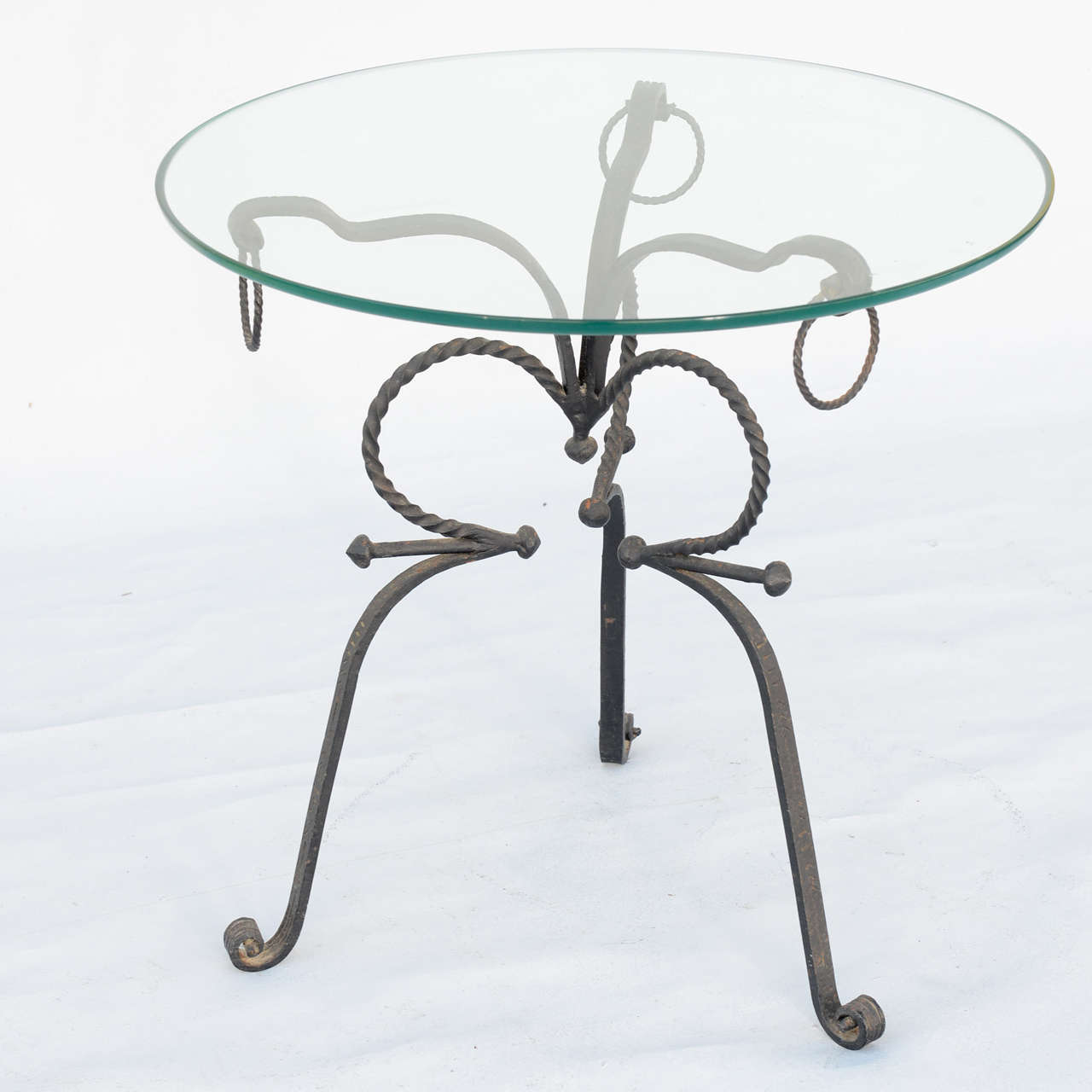Occasional table, having a top of round glass, on tripartite base of scrolling hand-wrought iron, each hock-leg decorated by rings and ending in scroll feet.  Stock ID: D3246