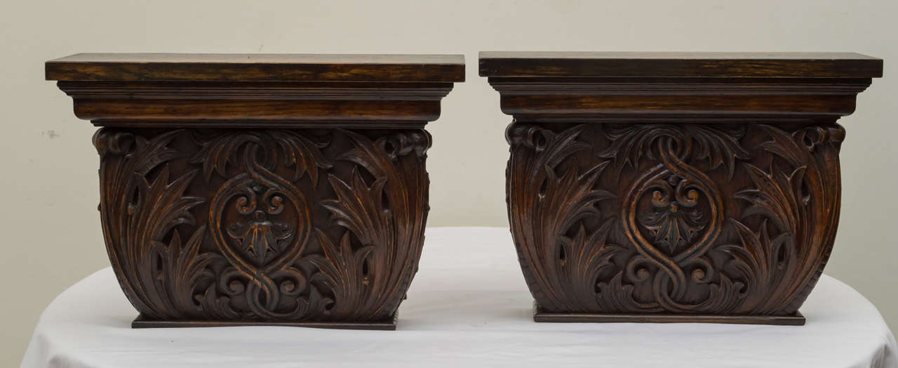 Pair of late 19th century American oak wall brackets composed from antique architectural elements. Solid high relief carved foliage on front and sides. Dark finish and reverse side with two brass hangers. There is a .25 inch difference in size due