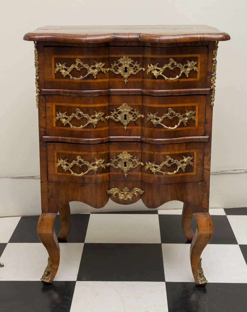 Diminutive 18th century German walnut Rococo commode. Stylish shaped top and front with figured walnut veneers. crossbanded top and drawers all fitted with gilt brass mounts. Three well-proportioned drawers over stout cabriole legs. Refinished,