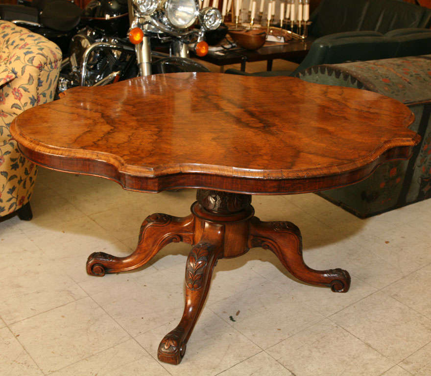 English center or breakfast table, with lozenge- shaped tilt-top in highly figured walnut, the quadrepod base carved with leaves and flowers.