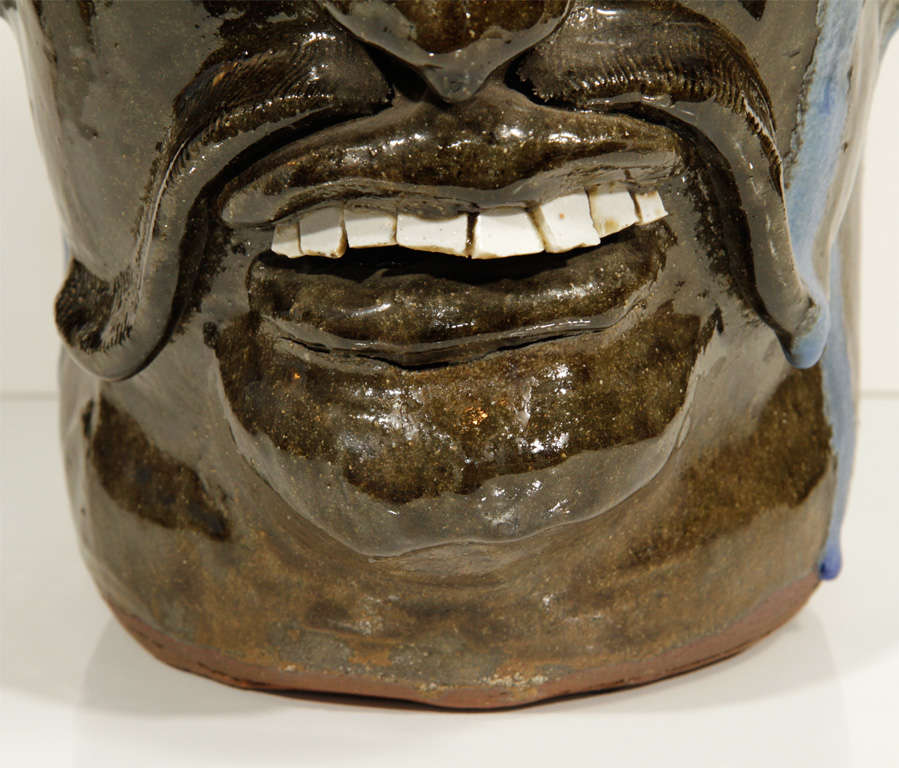 Extraordinary example alkaline glazed face jug by renowned folk artist Chester Hewell features fantastic details in the teeth, mustache and nose. Initialed on the handle and signed and dated on the bottom.