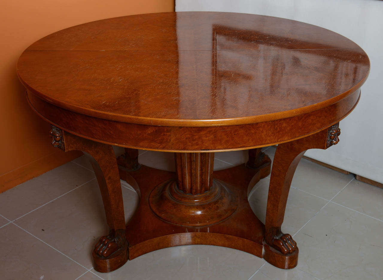 The circular top over curved tapering legs headed with carved lions faces and terminating in lion paw feet, with a central fluted column all on a plinth, separating to accept four original leaves to create a masterful dining table. Leaf is 21