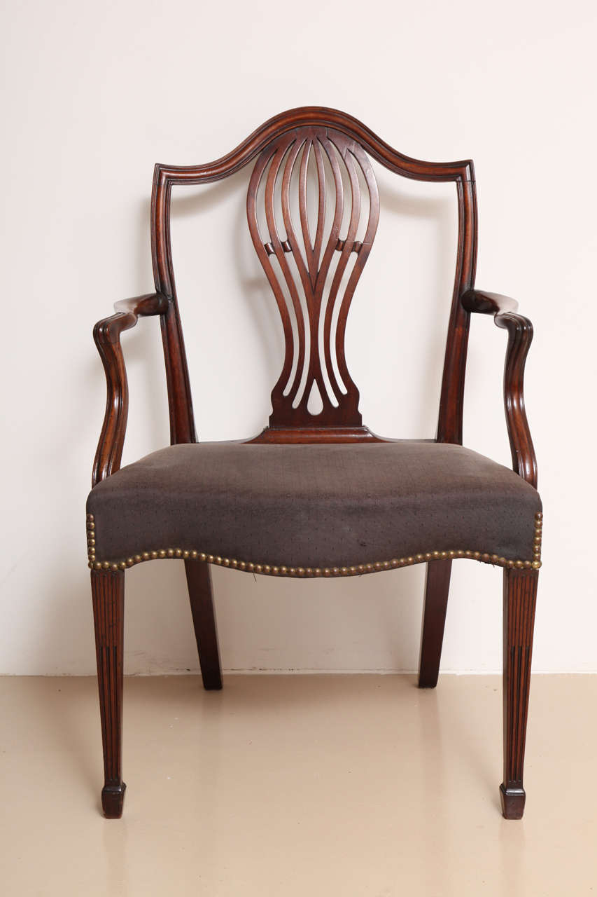 The back centered by a pierced vasiform splat and issuing moulded, downswept armrests, the over-upholstered serpentine-form seat raised on stop-fluted square tapering legs terminating in spade feet. Elegant proportions and design.