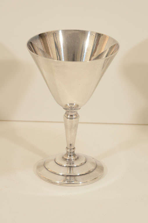 Silver plated cocktail glasses in classic Art Deco design. Possibly attributed to Keith Murray as it's similar in design to his 1 pint cocktail shaker. Signed Mappin & Webb Ltd.