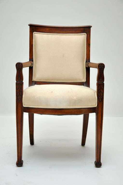 Pair of French mahogany fauteuils or armchairs from the consulate period. Mahogany frame with circular arm rests connecting trapeze shaped back, supported on front square tapered legs and saber back legs are out swept in the shape of a Calvary