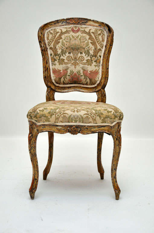 Pair of French Louis XV style side chairs, cartouche shaped back and shapely serpentine seat, floral silk upholstery, supported on front cabriole legs and back legs outswept, carved frame with foliage on crest and seat frieze.