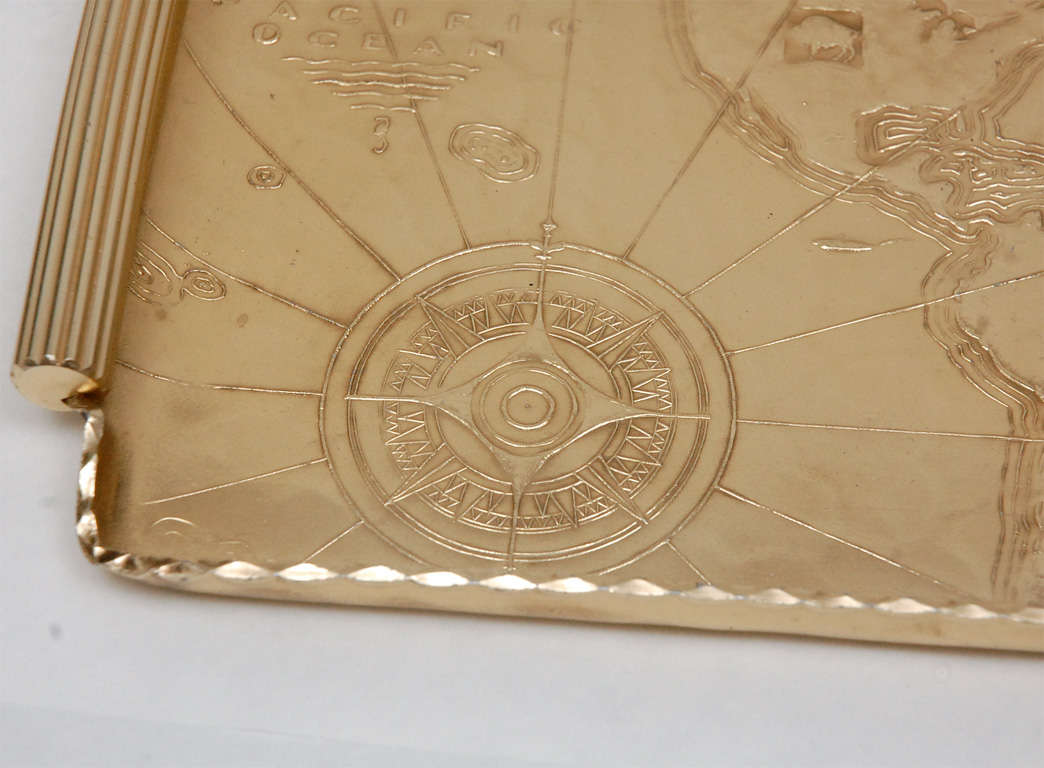A chic gold anodized aluminum repoussé map tray by Arthur Armour that features his maker's mark on the underside. Each of the continents features a native animal. Arthur Armour (1908-1998) began his hand wrought aluminum business in 1933 in Grove