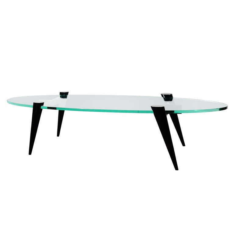 Mid-century modern cocktail table with elegant tapered leg design. Legs function as table bases in ebonized walnut wood. Fitted with thick hand bevelled elliptical or surfboard glass top. Ultra modern design great looking from all angles.