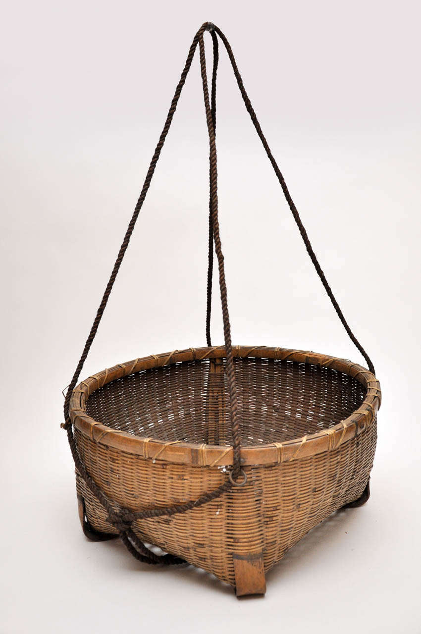20th century Japanese fishing basket. Beautifully woven with long rope handles. Handles extend approximately 2 feet past the top of the basket.