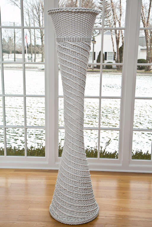 """Fabulous wicker plant stand in white paint.  Stand is 65.5"""" tall and 16"""" wide."""