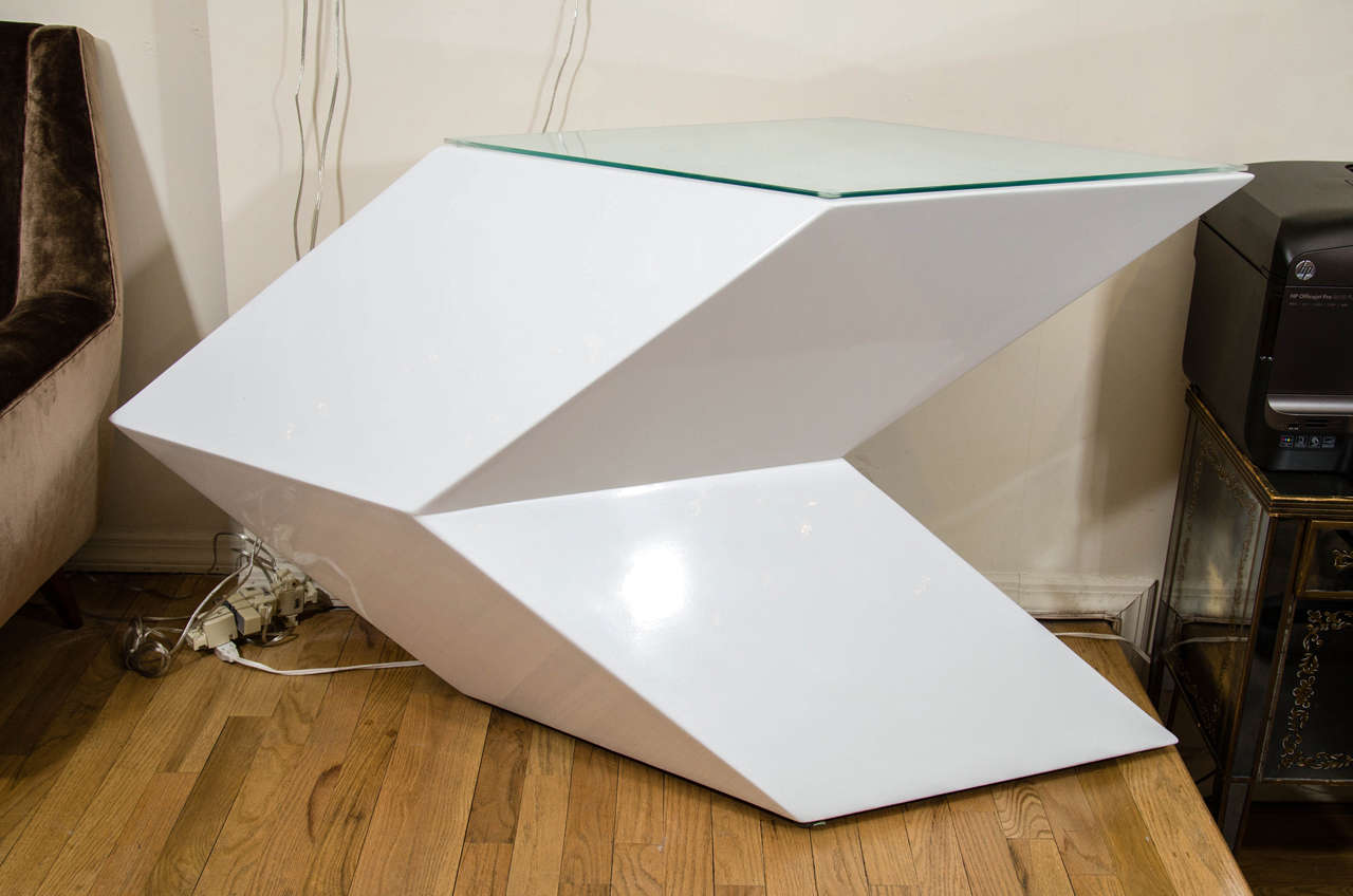 Angular cantilevered white lacquered wood console with glass top.