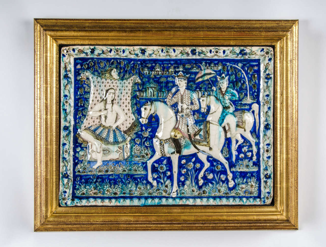 A large and splendid Qajar period tile depicting Khusrau, visiting Shirin; rectangular, moulded and decorated in polychrome depicting the famous moment in Person Literature of Shirin bathing in a pool as Khusrau gallops by with an attendant, the