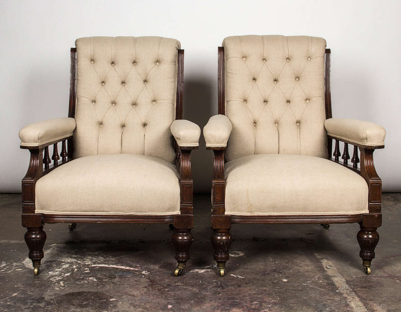 Rectangular button-tufted backrest with exposed frame sides over the rectangular seat flanked by padded and turned spindle arms. Covered in white linen fabric over turned legs and casters. Possibly late 19th century American.  Not available for