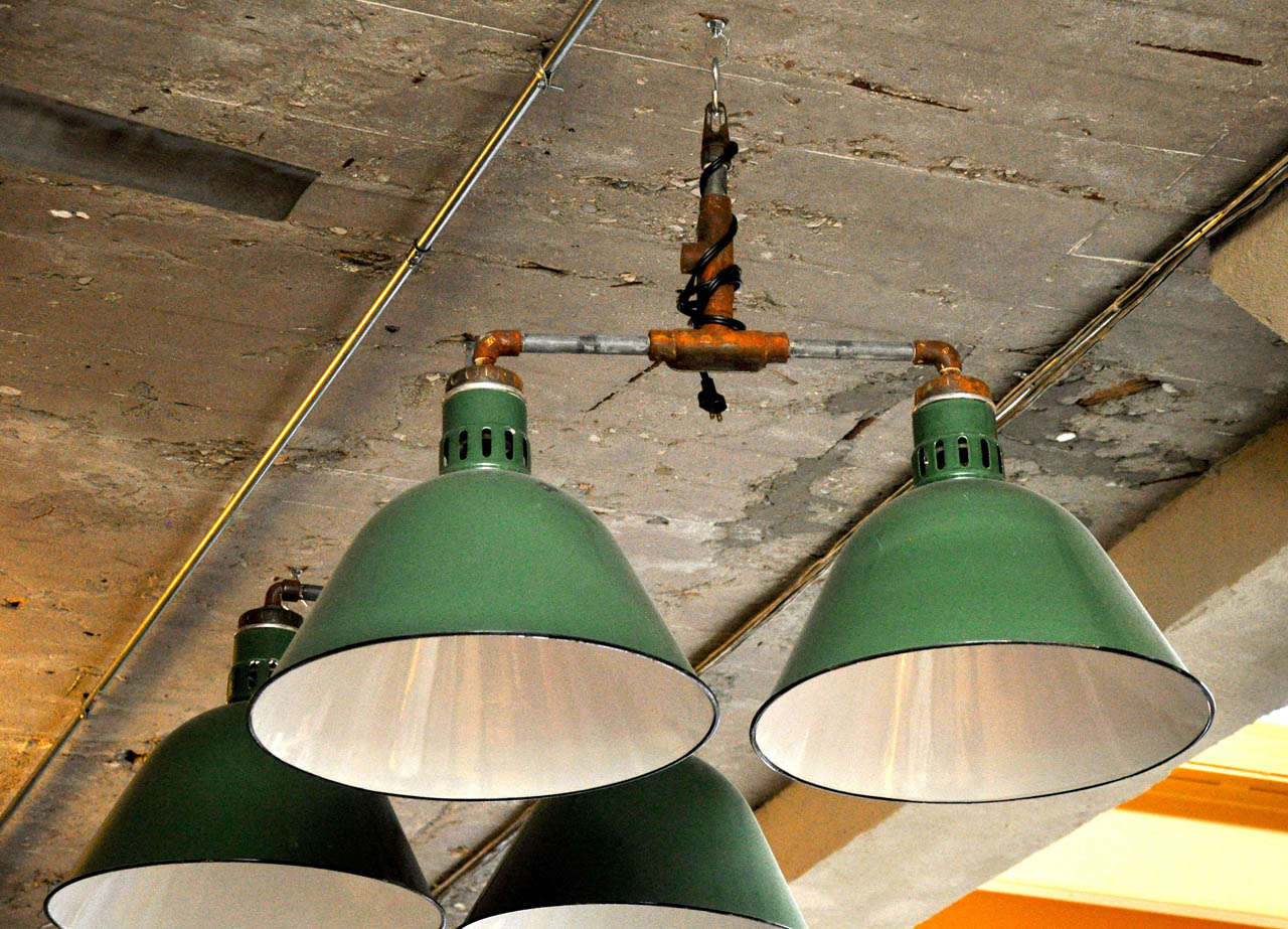 Dome shaped green and white enamel double pendant light fixtures from the mid-20th century.  Needs to be re-wired.