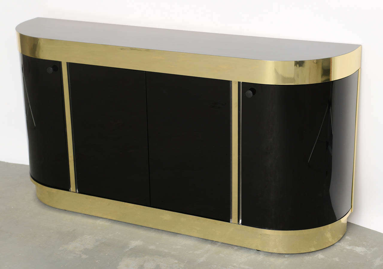 SOLD  Sleek and urbane, this slim profile console cabinet is very elegant and posh with black lucite doors, brass finished aluminum and black laminate top.  With elongated D form, this demi-lune has lucite curved side doors and center doors with