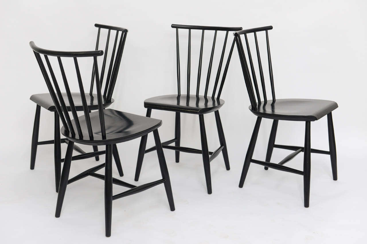 ...SOLD...With a nod to the Windsor chair, these four 1950s black ebonized chairs were made in Sweden.  Resembling as well the Ercol chair by Lucian Ercolani and others made in Denmark by Farstrup.  Great lean spindle back design.  Perfect for the