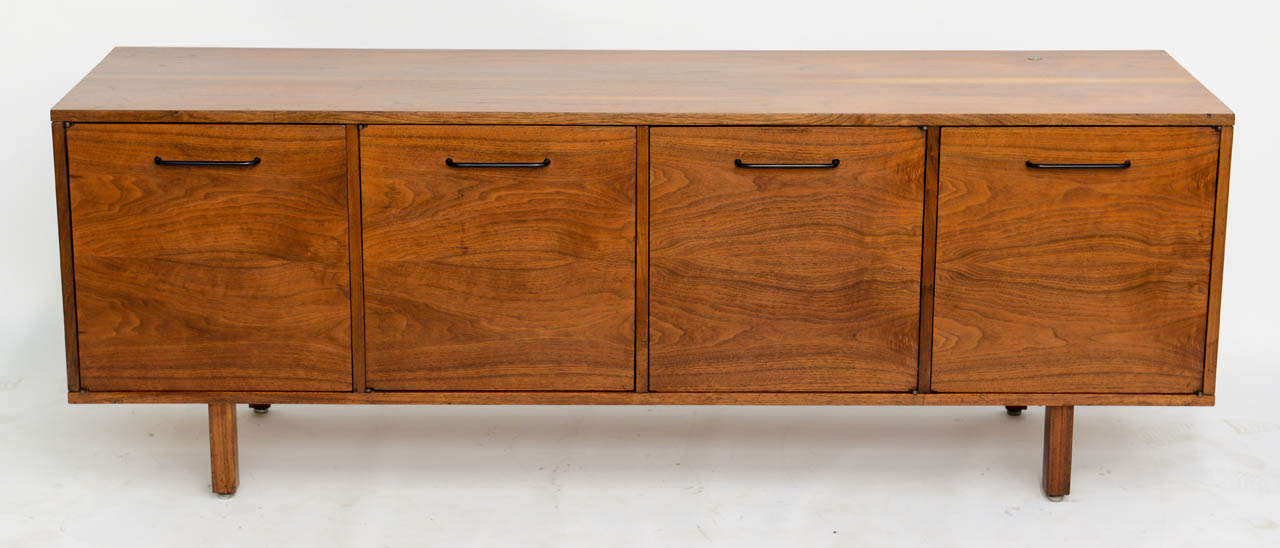 Splendid mid century modern Jens Risom credenza featuring fine figured walnut, with four doors opening to adjustable shelves. A keyed lock controlling all four doors should one want to lock. Wonderful low profile at 26