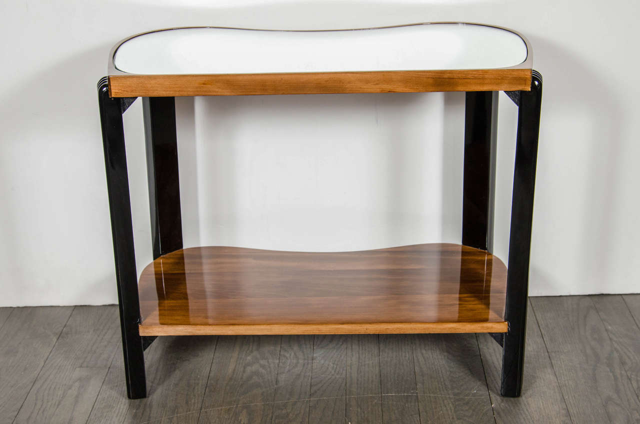 Art Deco Machine Age two-tiered side table with reeded leg design and inset mirrored top. This side tables features a bottom tier in book-matched Walnut and the top tier having an inset mirrored top while being framed in book-matched Walnut with