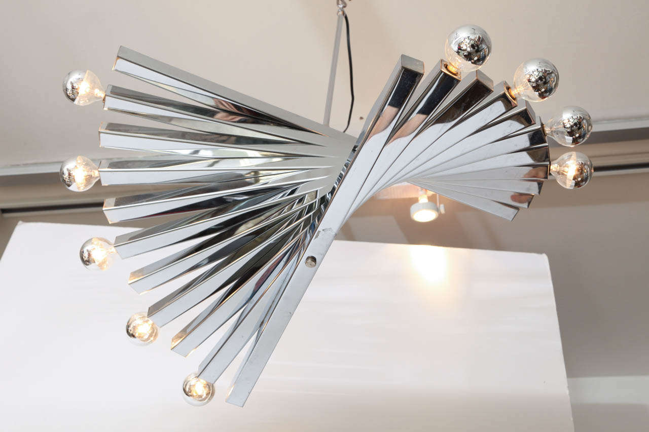 Spiral chrome chandelier by Gaetano Sciolari, Italy, circa 1960. The chandelier is made of square steel bars forming a partial spiral. It takes ten lights bulbs. The body of the chandelier is 11 inches high. Excellent vintage condition.