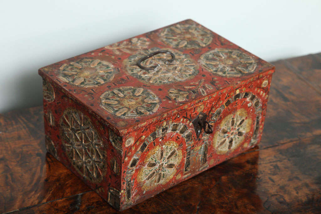 Very early paint and gesso decorated box, the wire hinged and handled top with flower head design, the petals executed in raised gesso and decorated in burnished (and now tarnished!) silver leaf on a red ground, the sides, back and front similarly