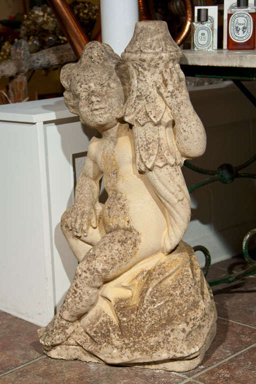 Sitting cast stone putti holding a torch.