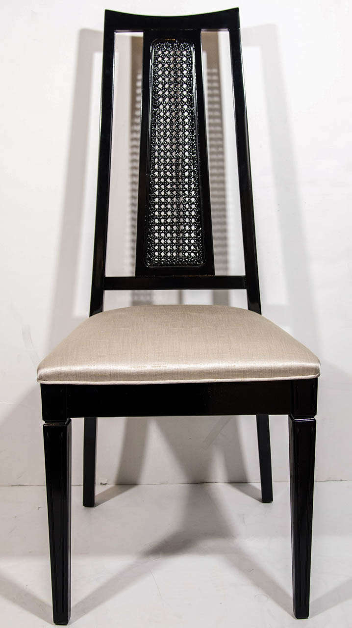 Set of four mid-century modern dining chairs with elegant high back design. The chairs have an trapezoid back with cut-out details and cane back center.  Ebonized walnut wood finish, and upholstered in champagne colored woven silk, with self welt