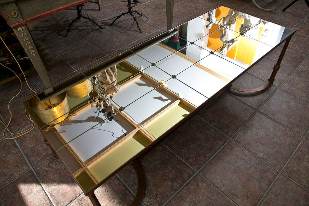 Neoclassical gilt metal coffee table, inset with fifteen mirrored glass panels and raised on round legs, joined by bowed stretcher.